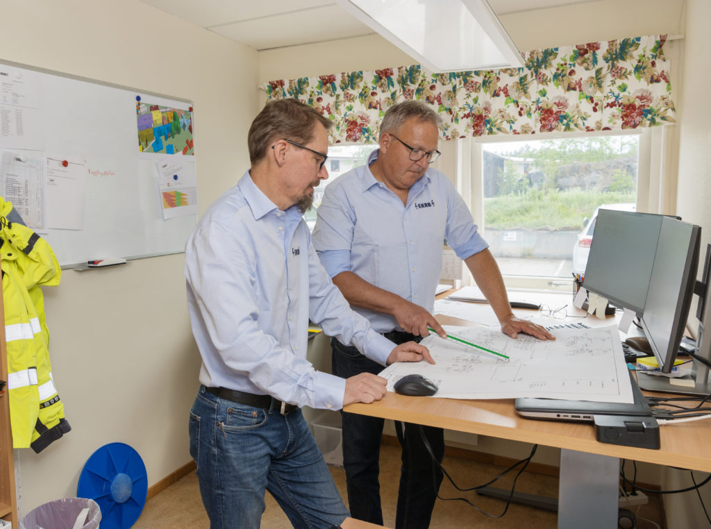 Two man looking at paper sheet